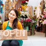 Girl holding open sign in front of florist